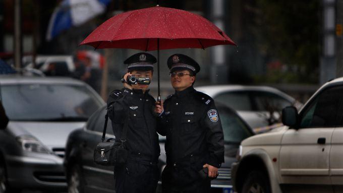 Chinesische Polizisten filmen Journalisten, die während eines Prozesses des Menschenrechtsanwalts Tang Jitian vor dem Gericht warten.