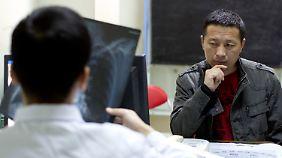 Ein Arzt betrachtet im April vergangenen Jahres das Röntgenbild des Anwalts Tang Jitian, nachdem dieser in Gefangenschaft Folter erfuhr.