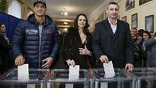 Vitali Klitschko (r.) zusammen mit seiner Frau Natalia und seinem Bruder Wladimir bei der Stimmabgabe.