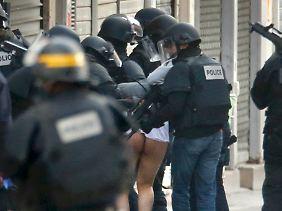 Sicherheitskräfte führen einen kaum bekleideten Mann ab.