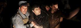Helfer bringen nach der Detonation Verletzte in Sicherheit.