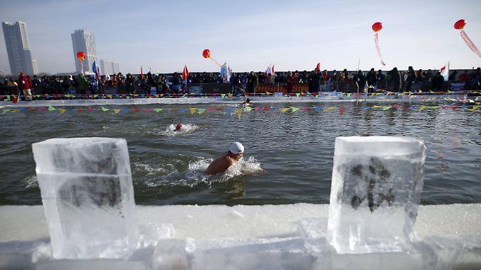 Das Internationale Schnee- und Eis-Festival ist eröffnet: In Harbin stürzen sich hartgesottene Teilnehmer  in die eiskalten Fluten.