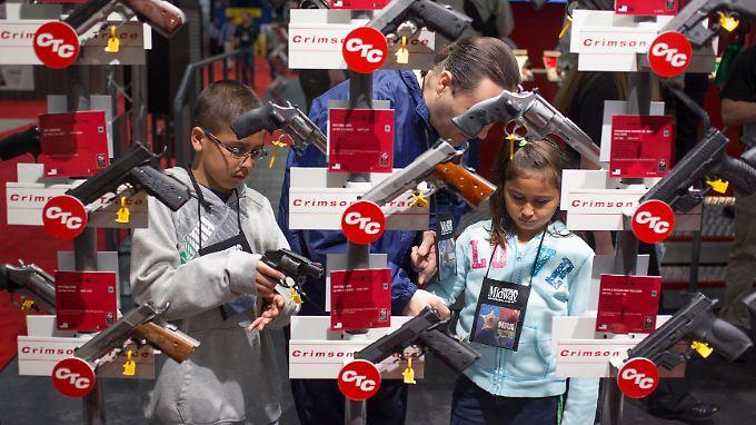 Eine Familie schaut sich bei einem NRA-Treffen Handwaffen an.