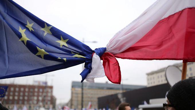 Regierungskritische Demonstranten in Polen haben ihre Landesflagge mit der EU-Flagge verknotet.