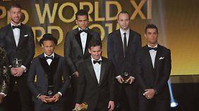 Erst schnappt ihm Lionel Messi (m.) die Trophäe weg, dann macht sich auch noch Dani Alves (m.h.) über Ronaldo (r.) lustig.
