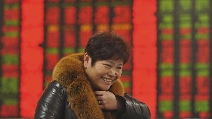 Gute Laune inmitten fallender Kurse: Eine Kleinanlegerin im chinesischen Fuyang.