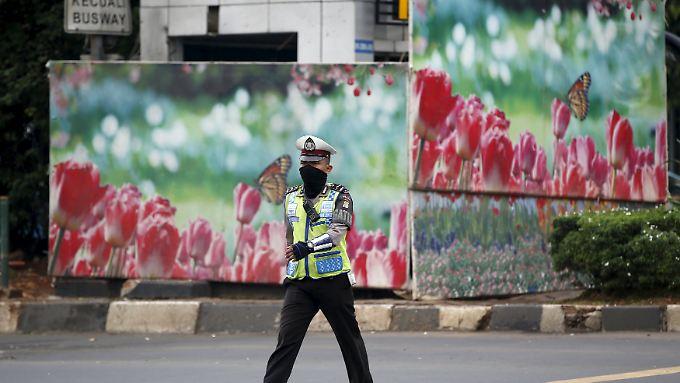 Blumen statt Blut: Bunte Bilder verdecken die zerstörte Polizeiwache in Jakarta.