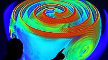 Ein Mitarbeiter des Max-Planck-Instituts für Gravitationsphysik in Potsdam erläutert anhand einer Computersimulation die Ausbreitung von Gravitationswellen. Foto: Michael Hanschke/Archiv
