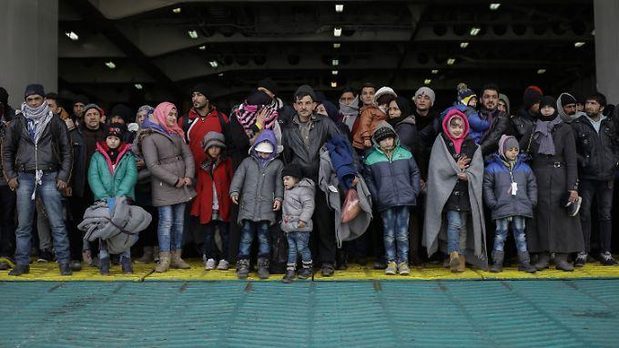 Flüchtlinge kommen an Bord einer Fähre im Hafen von Piräus an.