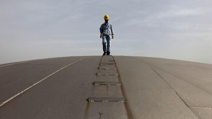 Preiseinbruch: Ein Arbeiter des chinesischen Öl-Riesen Sinopec geht auf einem Öltank.