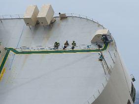Extreme Schlagseite: Die Bergungsexperten warten nach ihrem Einsatz an Deck im Liegen auf die Seilwinde des Hubschraubers.