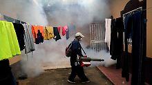Mit Insektenvernichtungsmitteln ausgerüstet ziehen die Menschen in Honduras durch die Straßen.