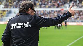 """St. Paulis Trainer Ewald Lienen mit einer Sonder-Trainingsjacke mit der Aufschrift """"Kein Fußball des Faschisten""""."""