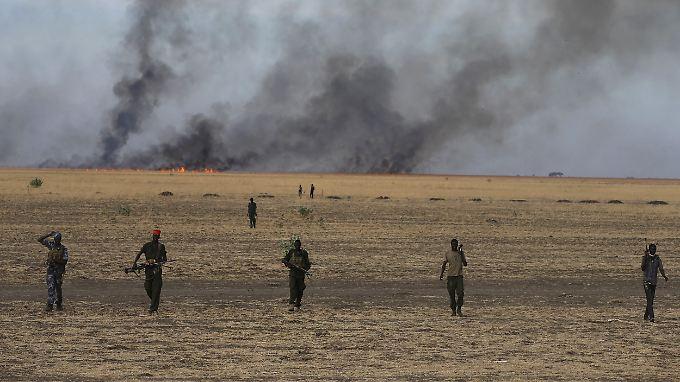 Die Lage im Südsudan ist extrem unübersichtlich - wer für das Massaker an den Zivilisten verantwortlich ist, ist nicht klar. Hier marschieren Rebellensoldaten in breiter Linie vor einem selbst gelegten Buschfeuer.