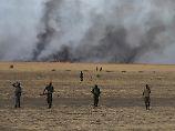 Rebellensoldaten marschieren in breiter Linie vor einem selbst gelegten Buschfeuer: Die Lage im Südsudan ist extrem unübersichtlich - wer für das Massaker an den Zivilisten verantwortlich ist, ist nicht klar.