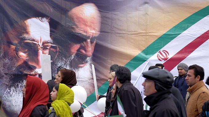 Feierlichkeiten zum 37. Jahrestag der Islamischen Revolution am 11. Februar in Teheran. Auf dem Plakat die Konterfeis vom verstorbenen Gründer der Islamischen Republik, Ayatollah Ruhollah Khomeini (r), und dem heutigen Obersten Religionsführer Ayatollah Ali Khamenei.