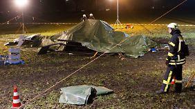 Scheinwerfer der Feuerwehr leuchten die Absturzstelle aus: Die Überreste des Hubschraubers liegen unter der Plane.