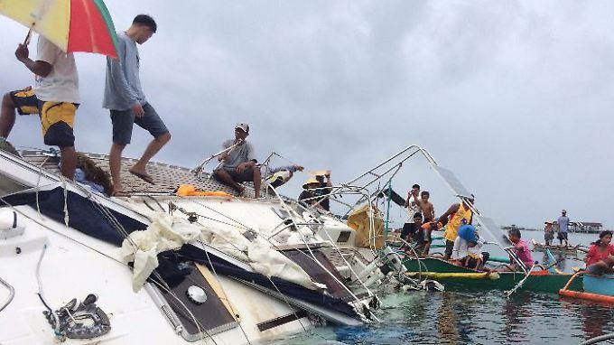 Philippinische Fischer zogen das havarierte Schiff bis an die Küste.