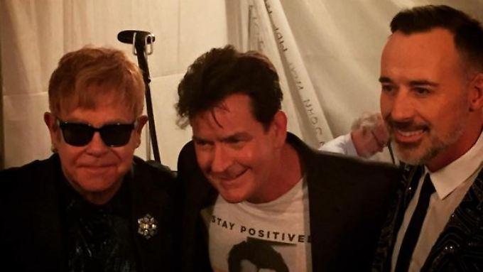 Mit seinem T-Shirt sammelt Charlie Sheen (M.) Geld für die Aids-Stiftung von Elton John (l.).