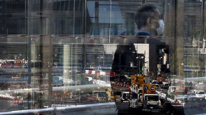 Ein Geschäftsmann spiegelt sich in einer Schaufensterscheibe vor einer Baustelle in Tokio.