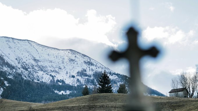 Ein Kreuz eines alten Grabes ist auf dem Friedhof in Le Vernet (Frankreich) zu sehen. Im hinteren Teil befindet sich die Gemeinschaftsgrabstelle für die Opfer des Absturzes vom Germanwingsflug 4U9525.