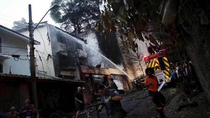 Feuerwehrleute versuchen eines der Häuser zu löschen, auf die das Flugzeug gestürzt ist.