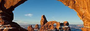 Der Turret Arch und der North Window Bogen, hier im Bild, sind zwei der massiven Steinbögen in der sogenannten Windows Section des Arches Nationalparks. Die Felsformationen sind besonders bei Sonnenauf- und Untergang außergewöhnlich fotogen: Das Sonnenlicht lässt das Gestein dann noch röter erscheinen.