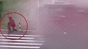 Crash an Kreuzung in China: Motorradfahrer rettet sich vor schleuderndem Lkw
