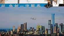 Ein Arbeiter blickt über einen Bauzaun im Business District von Peking.