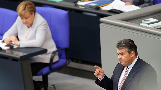 Der Vizekanzler und seine Kanzlerin: Gabriel bei seiner Rede, Merkel hört zu.