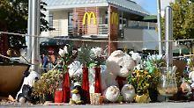 Die Opfer bleiben unvergessen: Blumen und Stofftiere liegen gegenüber einer McDonald's-Filiale auf dem Gehweg vor dem Olympia-Einkaufszentrum in München.