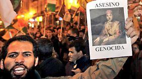 Ein Mann protestiert gegen die Räumung des Lagers. Auf dem Plakat ist der marokkanische König Mohammed VI. in einer Naziuniform zu sehen.