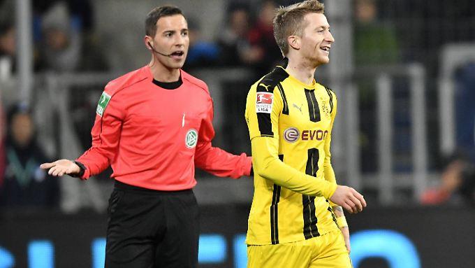 Reus muss über seinen Platzverweis schmunzeln, BVB-Boss Watzke schimpft.