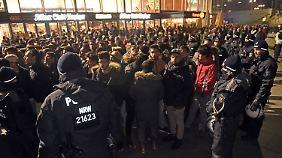 Eine Menschenmenge, eine Polizeikette - der Silvesterabend in Köln. Im Hintergrund ist die Bahnhofshalle zu sehen.