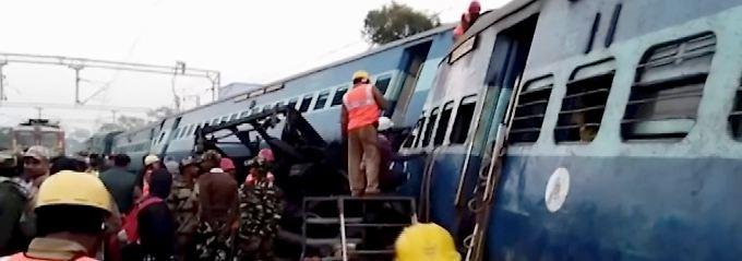 Rettungskräfte versuchen, Menschen aus dem Zug zu befreien.