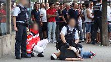 Polizisten nehmen den am Boden liegenden Mann fest, der zuvor eine Frau mit einer Machete getötet haben soll.