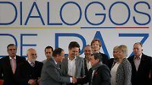 Der ELN-Vertreter Pablo Beltran (vorne rechts) schüttelt dem Gesandten der kolumbianischen Regierung, Juan Camilo Restrepo, die Hand.