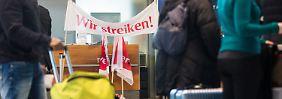 """""""Wir streiken"""" steht am 08.02.2017 im Terminal 3 am Flughafen in Stuttgart (Baden-Württemberg) auf einem Banner des Bodenpersonals der Stuttgart Ground Services (SGS), während davor Passagiere lange auf den Check-In für ihre Koffer warten. Wegen der Warnstreiks kommt es heute an den Flughäfen in Stuttgart, Berlin und Hamburg zu Ausfällen und starken Verzögerungen. Foto: Christoph Schmidt/dpa +++(c) dpa - Bildfunk+++"""