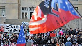 Ein Kundgebung von Neonazis in Kansas City: Im Vordergrund weht eine Flagge mit Hakenkreuz darauf, im Hintergrund sind Gegenproteste zu sehen.