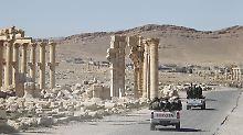 Syrische Soldaten fahren durch die Ruinen der antiken Stätten von Palmyra.