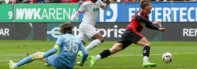 Gleich fällt er: Augsburgs Marwin Hitz bringt den Freiburger Mike Frantz per Grätsche zu Fall.