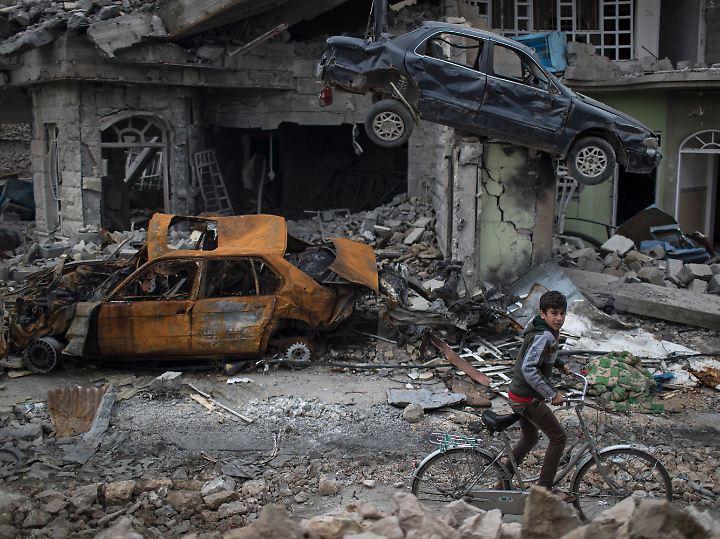 Ein Junge fährt auf einem Fahrrad durch eine stark zerstörte Straße im Westen Mossuls.