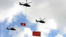 Helikopter haben zur zur 15-Jahres-Feier der Übergabe der ehemaligen britischen Kolonie im Jahr 2012 die Flaggen Hongkongs (l.) und Chinas im Schlepptau.