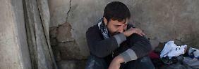 Dieser Mann ringt bei den Aufräumarbeiten nach einem Luftangriff mit den Tränen.