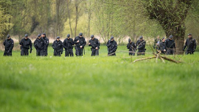 Brutaler Überfall: Schritt für Schritt suchen Polizisten einer Einsatzhundertschaft in den Siegauen bei Bonn nach Spuren.