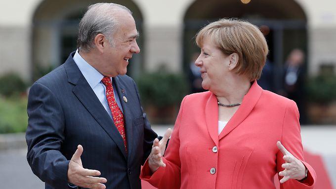 OECD-Chef Ángel Gurría und Kanzlerin Merkel verteidigen offene Märkte.
