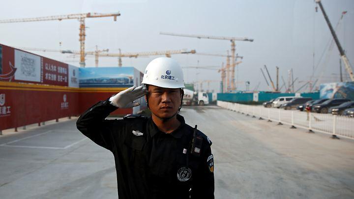 Ein Sicherheitsbeamter salutiert vor der Baustelle des neuen Flughafens in Peking.