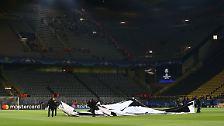 Ordner räumen die Champions-League-Plane vom Rasen, sie soll erst am Mittwoch wieder ausgelegt werden.