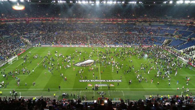 Hunderte Lyon-Fans flüchteten vor dem Spiel nach Feuerwerksattacken türkischer Anhänger auf den Rasen.