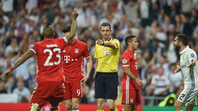 Schiedsrichter Viktor Kassai gestikuliert neben Arturo Vidal, Robert Lewandowski und Thiago Alcantara von Bayern München sowie Dani Carvajal von Real Madrid.
